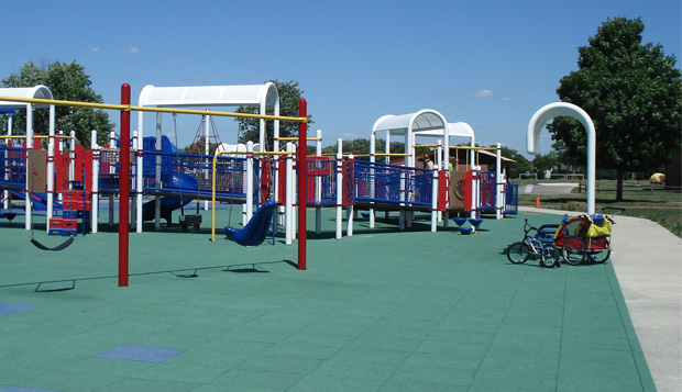 The entire perimeter of the playground is flush level with the playground surface so users can access the playground equipment from various locations at the park.
