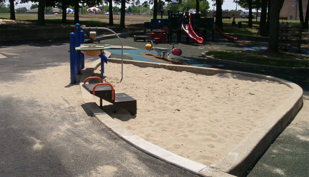 This sand play area is designed with a play table, transfer system and raised edge to give children the option of playing seated from a wheelchair, transfering to the raised edge or using the transfer system to play in the sand.